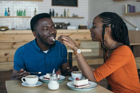 Photo for African american woman feeding boyfriend with dessert on romantic date in cafe - Royalty Free Image