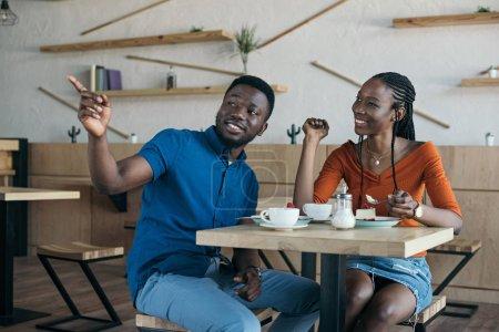 Photo pour Couple afro-américain assis à table avec les tasses de café et des desserts au café - image libre de droit