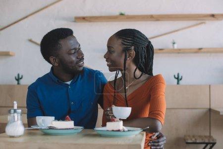 Photo pour Portrait de couple afro-américain regardent tout en restant assis à table avec les tasses de café et des desserts au café - image libre de droit