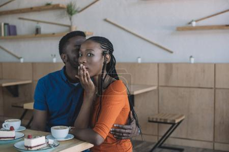 Photo for African american man telling secret to shocked girlfriend at table in cafe - Royalty Free Image