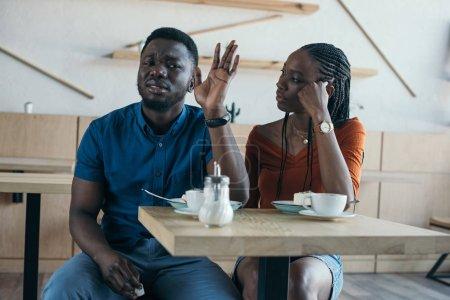 Photo pour Insulté afro-américain assis à table avec petite amie dans le café - image libre de droit