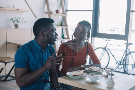 insulted african american man sitting at table with girlfriend in cafe