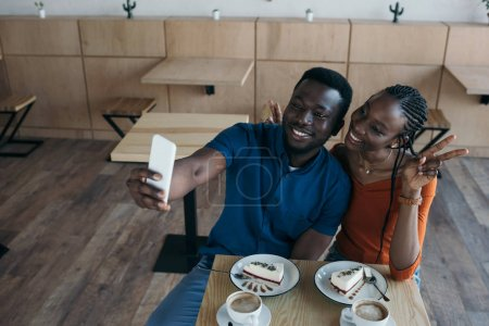 smiling african american couple taking selfie on smartphone together in coffee shop