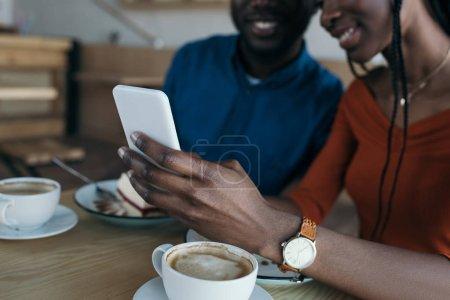 recadrée tir du couple afro-américain utilisant smartphone ensemble au café