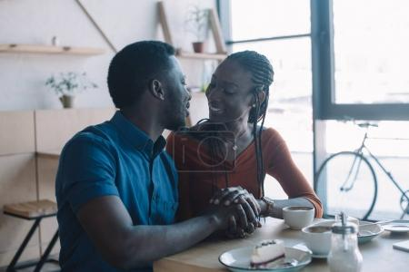 smiling african american couple holding hands and looking at each other on romantic date in coffee shop