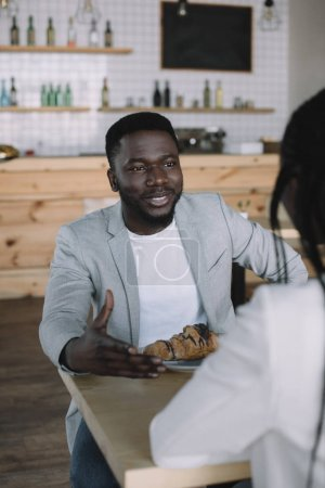 partial view of african american man spending time with friend in cafe