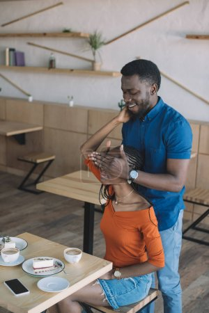 african american man covering girlfriends eyes to surprise her in coffee shop