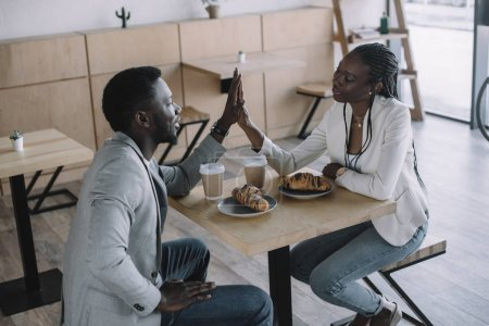 african american friends giving high five to each other at table in cafe