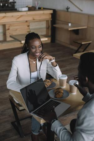 smiling african american friends sitting at table with laptop in coffee shop
