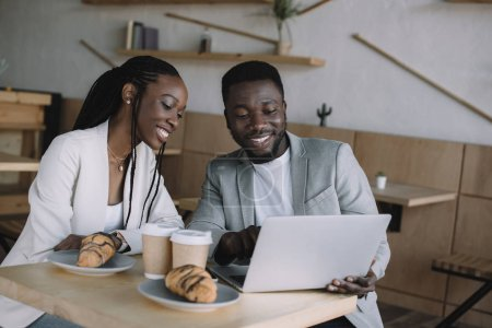 portrait of smiling african american friends using laptop together at table in cafe