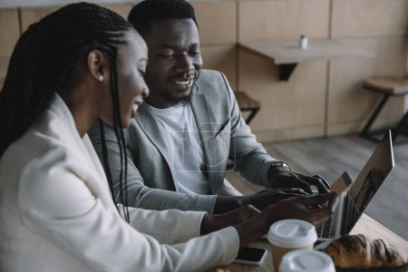 smiling african american friends shopping online together at table in cafe