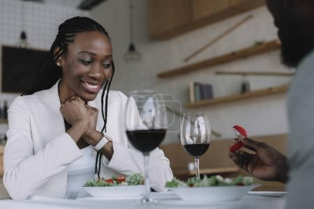 vue partielle de l'afro-américain propose de copine lors de rendez-vous romantique au restaurant