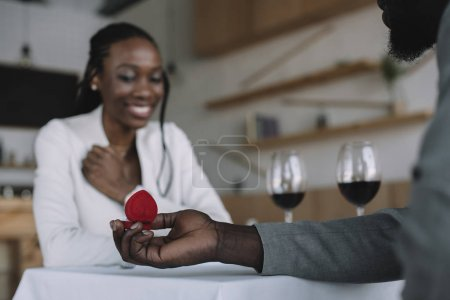 partial view of african american man proposing to girlfriend during romantic date in restaurant