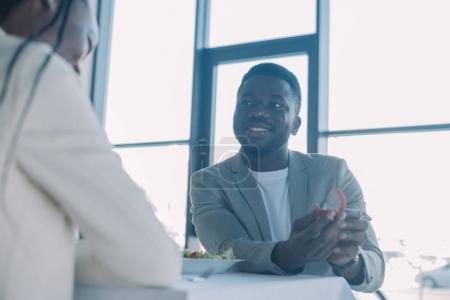 Foto de Vista parcial del sonriente hombre afroamericano propone a novia durante cita romántica en el restaurante - Imagen libre de derechos