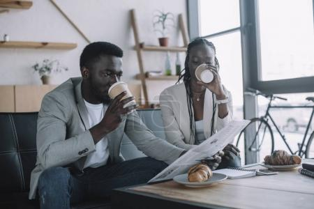 african american businesspeople drinking coffee to go while reading newspaper in coffee shop
