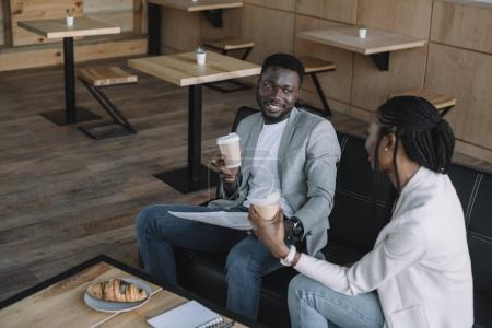 african american businesspeople with coffee to go during meeting in cafe