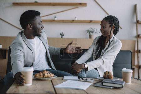 Photo pour Vue de côté de partenaires d'affaires afro-américain dont la conversation à table à café - image libre de droit