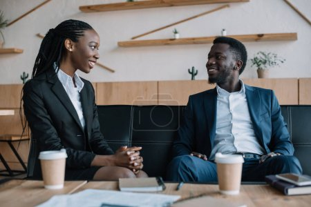portrait of smiling african american business partners looking at each other in cafe
