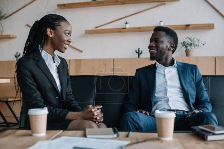 Portrait de sourire afro-américaine partenaires regardent dans café