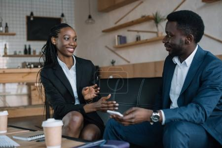 portrait of smiling african american business partners having conversation in cafe