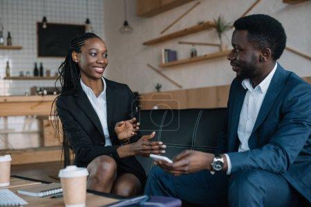 Photo pour Portrait de souriants partenaires d'affaires afro-américains en conversation dans un café - image libre de droit