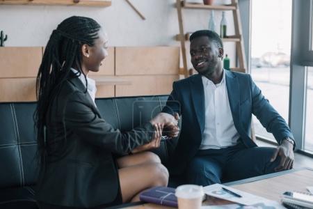 Photo pour Partenaires d'affaires afro-américains serrant la main lors d'une réunion dans un café - image libre de droit