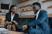 portrait of smiling african american business partners in cafe