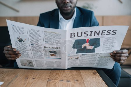 partial view of african american businessman with newspaper in cafe