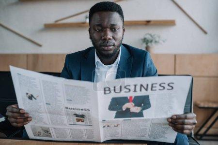 Photo pour Portrait d'un homme d'affaires afro-américain lisant un journal dans un café - image libre de droit