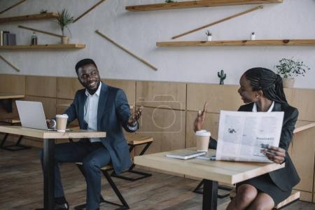 Afrikanisch-amerikanischer Geschäftsmann arbeitet am Laptop, während Kollege Zeitung im Café liest