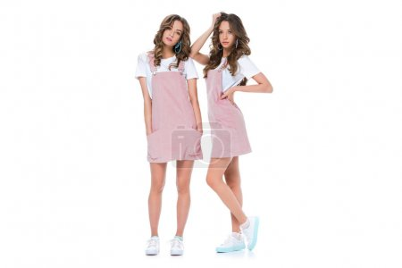 Photo for Beautiful young twins posing in pink dresses and shirts isolated on white - Royalty Free Image