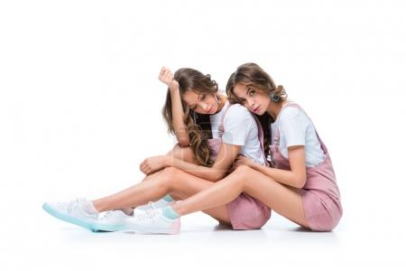 attractive young twins sitting and hugging on white