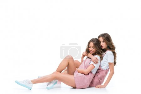 happy beautiful young twins sitting and hugging on white
