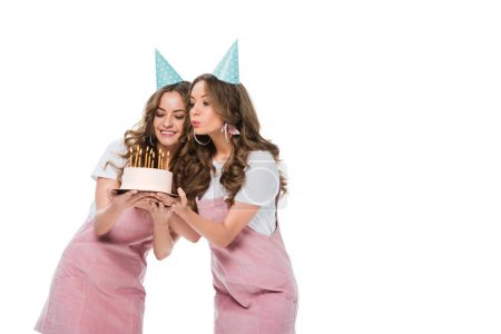 happy beautiful young twins blowing out candles on birthday cake isolated on white