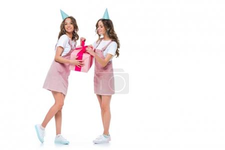 happy beautiful young twins holding one birthday gift isolated on white
