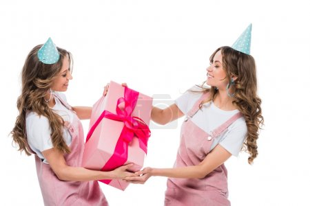 happy beautiful young twins holding one birthday present isolated on white