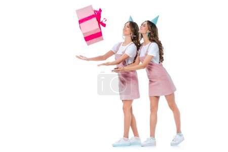 beautiful young twins catching falling present box isolated on white