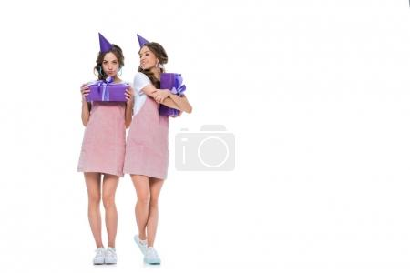 beautiful young twins in birthday caps holding presents isolated on white