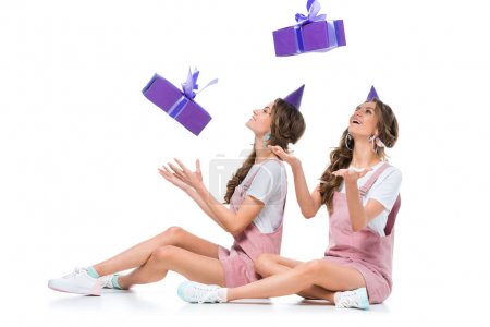happy beautiful young twins catching falling present boxes on white