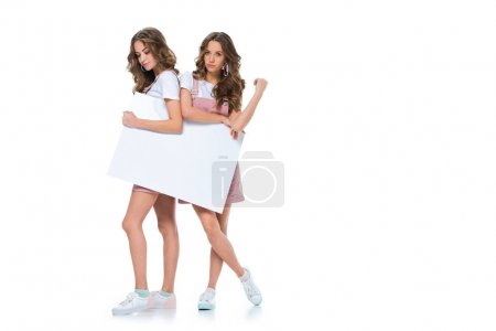 attractive young twins holding empty greeting card isolated on white