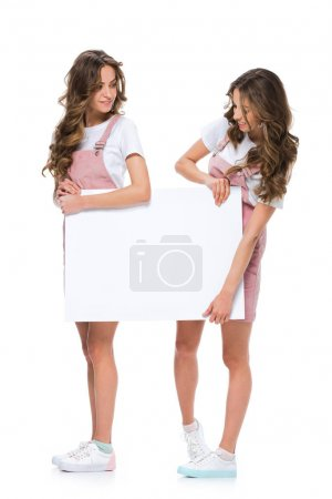 attractive young twins holding blank placard isolated on white