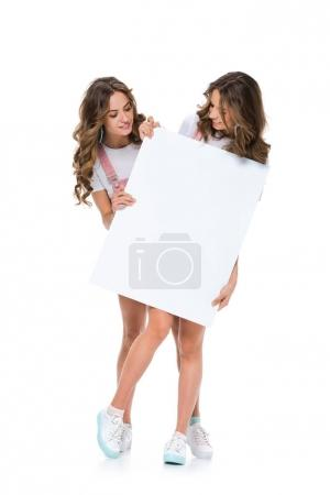attractive young twins looking at empty board isolated on white