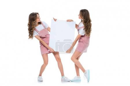Photo for Happy attractive young twins holding empty board isolated on white - Royalty Free Image