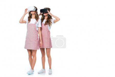 young twins using virtual reality headsets isolated on white