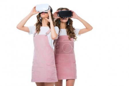 young twins watching something in virtual reality headsets isolated on white