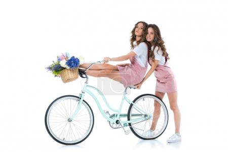 attractive young twin holding sister on bicycle on white