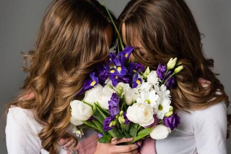 twins covering faces with bouquet isolated on grey