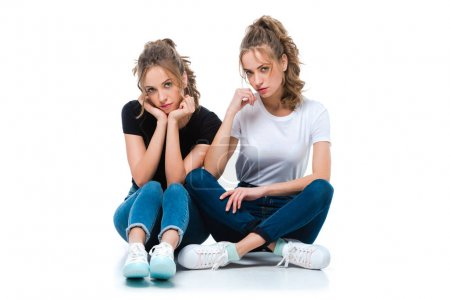 attractive young twins sitting on floor and looking at camera on white