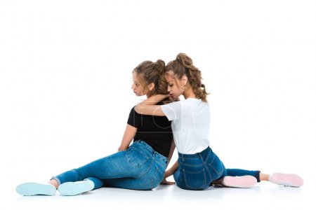 Photo for Back view of attractive young twins hugging and sitting on floor on white - Royalty Free Image