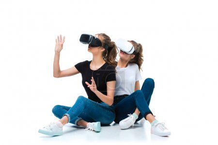 Photo for Young twins touching something with virtual reality headsets on white - Royalty Free Image